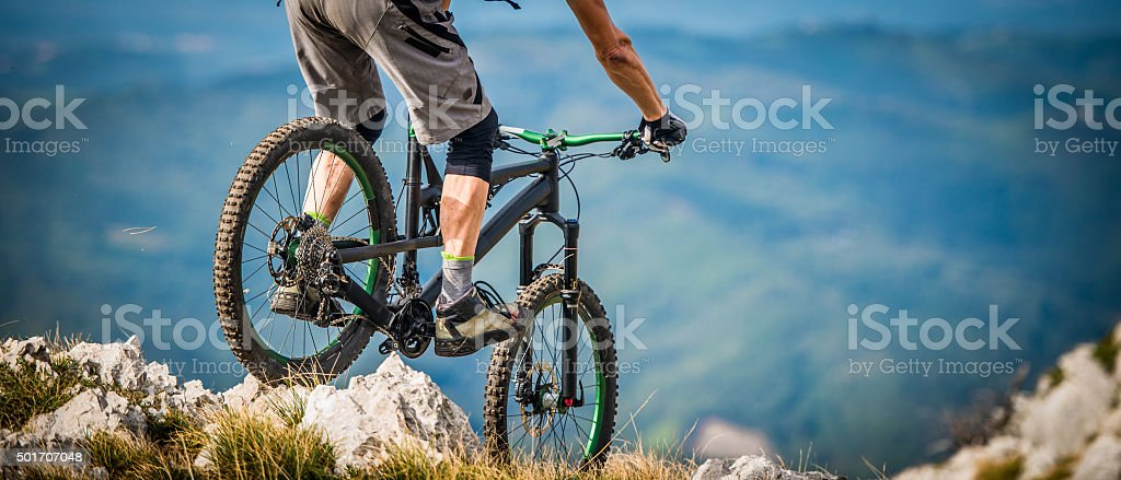 Mountain biker riding across rocks on a moutain stock photo