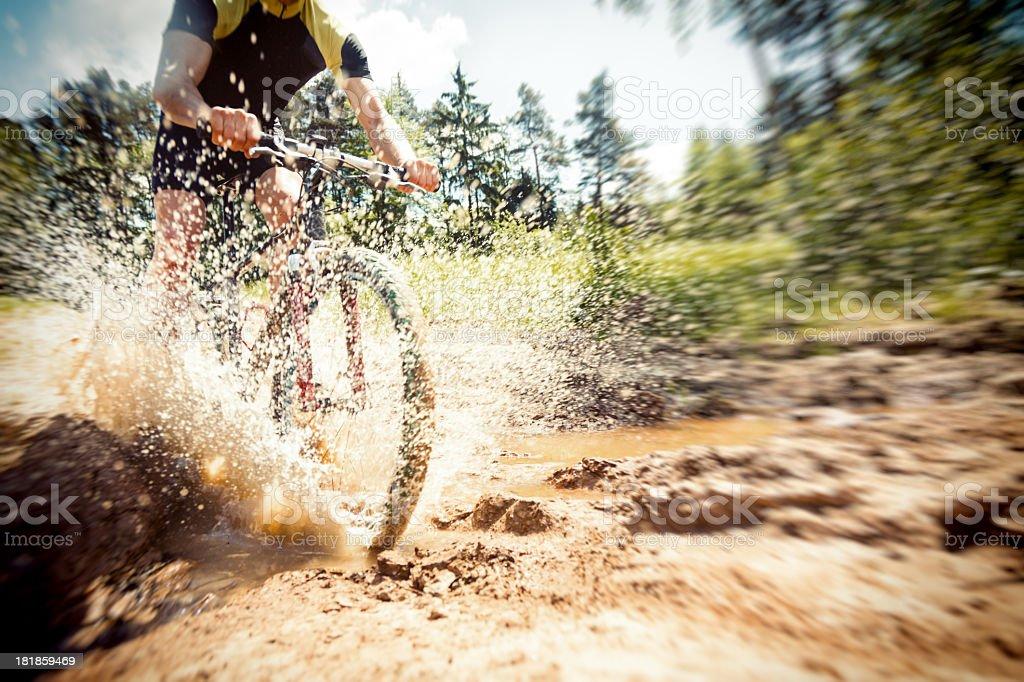 mountain biker riding through a dirty puddle stock photo
