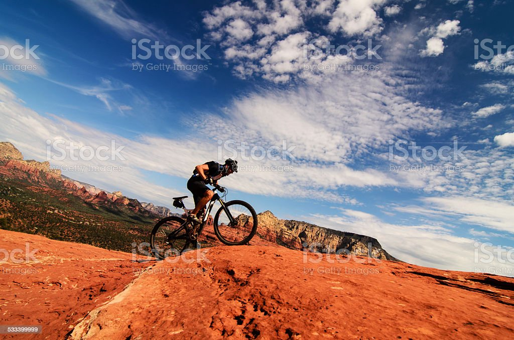 Mountain biker riding uphill in desert stock photo