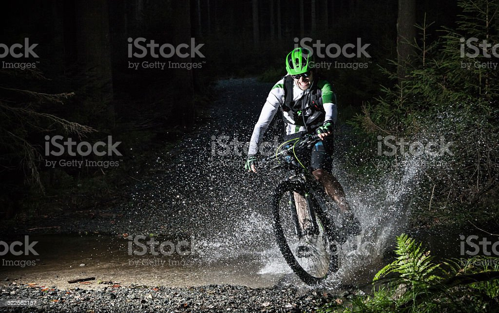 Mountain biker speeding through forest stream. stock photo