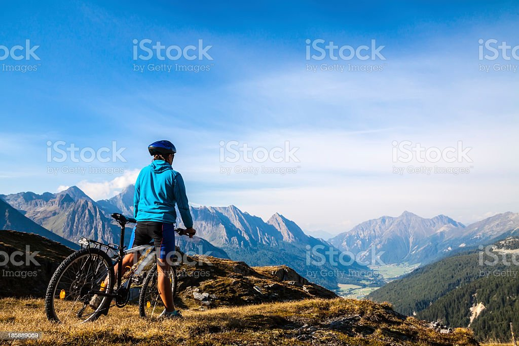 Mountain biker stopped on rocky hillside stock photo