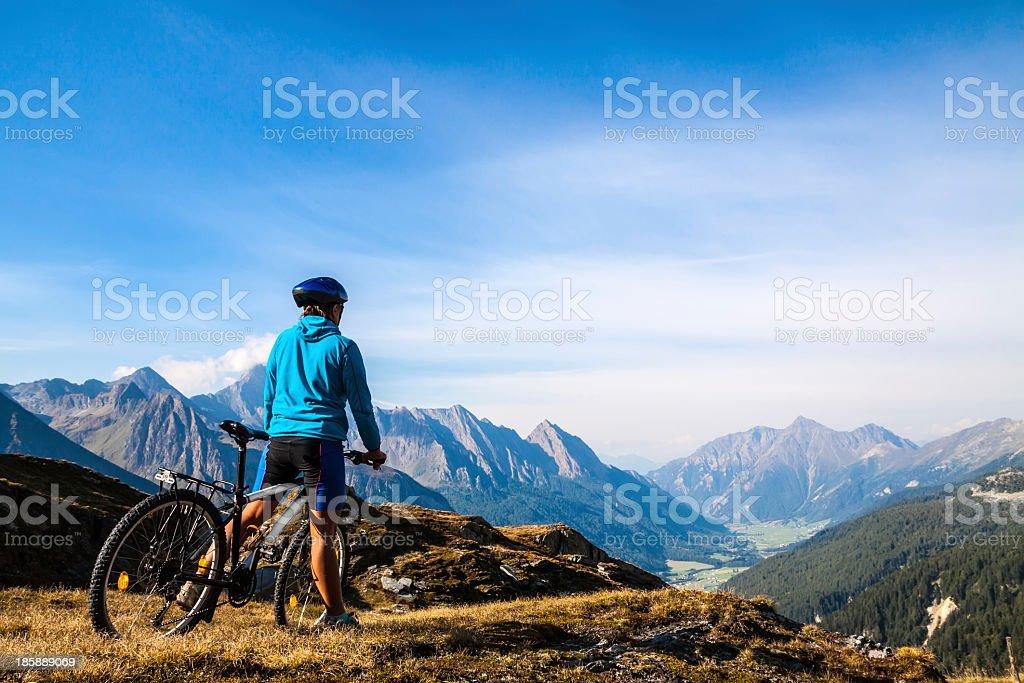 Mountain biker stopped on rocky hillside stock photo