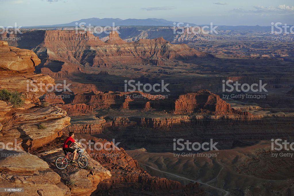 Mountain Biker Stopped on Rocky Ledge to Look At View royalty-free stock photo
