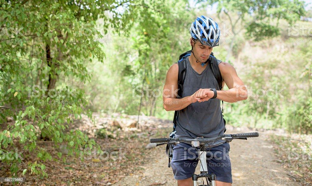 Mountain biker using a smart watch stock photo