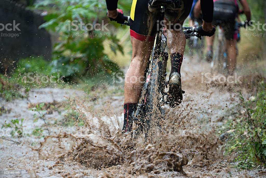 Mountain bikers driving in rain upstream creek stock photo