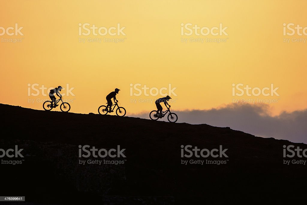 Mountain bikers going downhill at sunrise. royalty-free stock photo