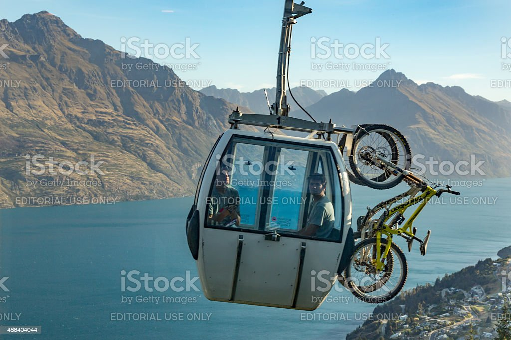Mountain Bikers in Skyline Gondola Going Over Queenstown City stock photo