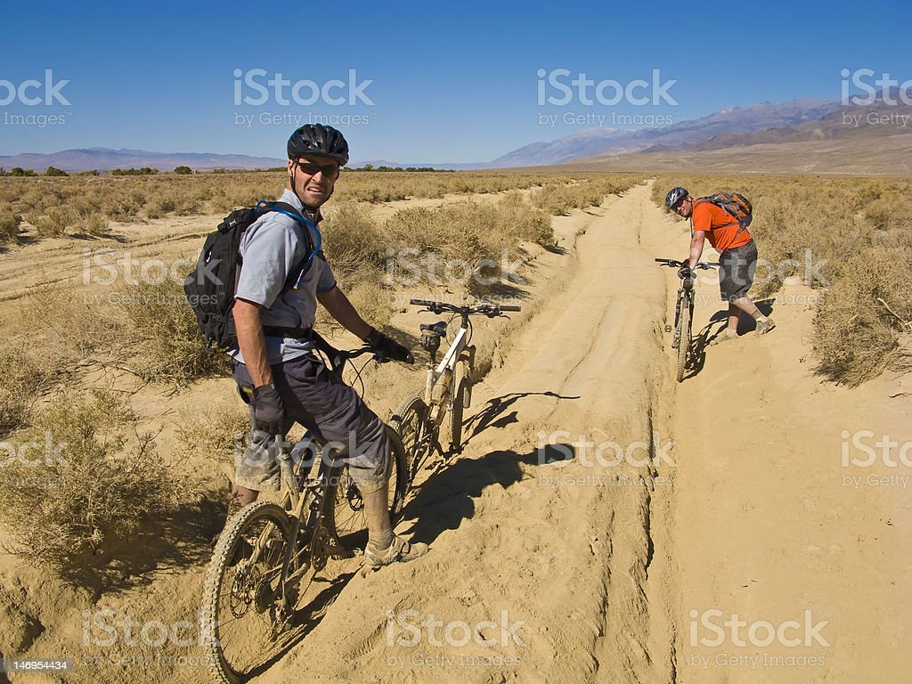 Mountain bikers stuck in sand. stock photo