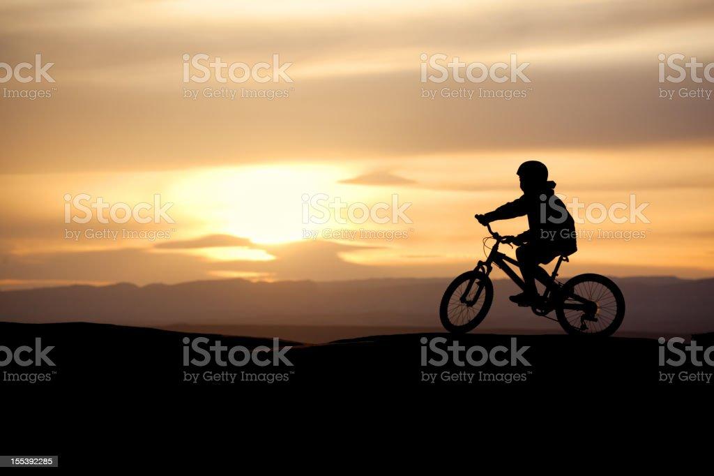 mountain biking boy silhouette stock photo