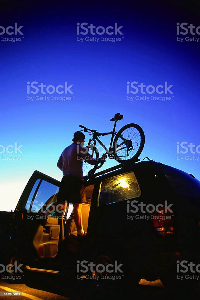 mountain biking man loading bike on SUV twilight sky stock photo