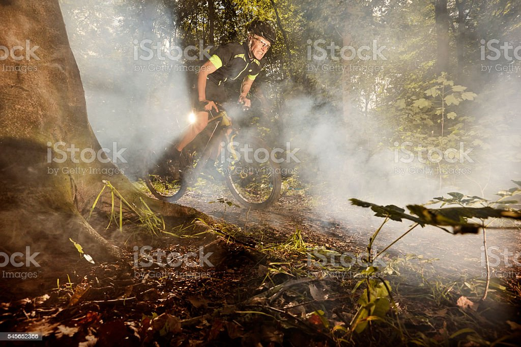 Mountain Biking racing in hazy forest stock photo