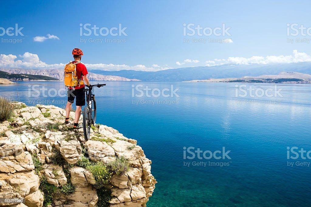 Mountain biking rider looking at inspiring sea and mountains stock photo
