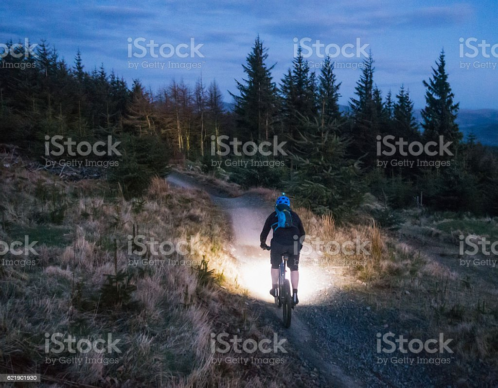 Mountain biking with lights at dusk stock photo