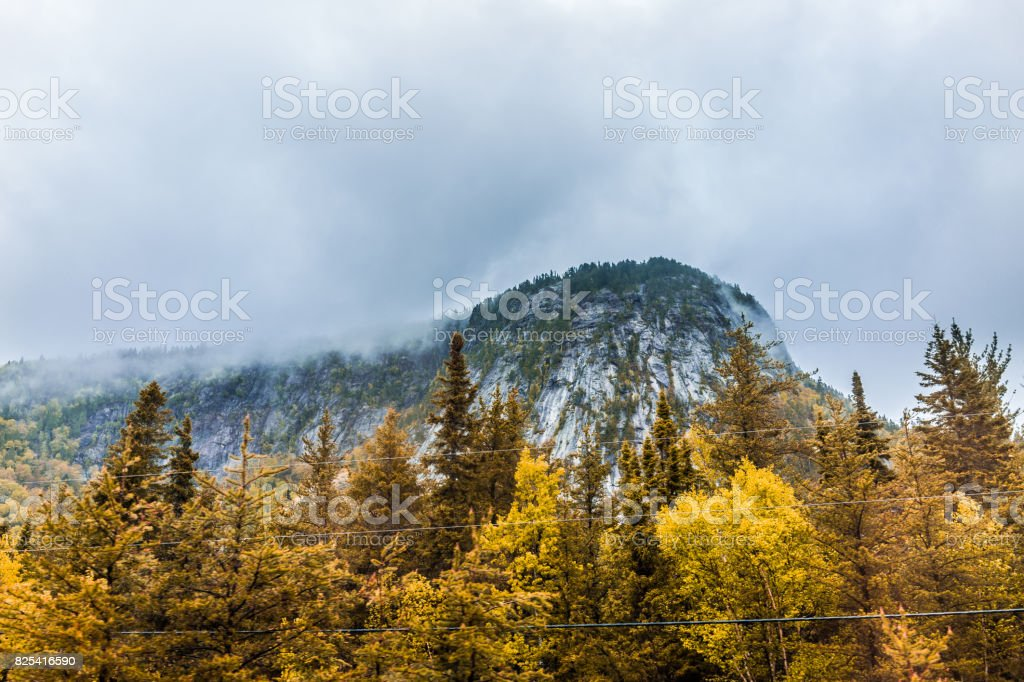 Mountain cliff by highway road with wires in stormy misty and foggy weather in mountain Charlevoix region of Quebec, Canada during autumn stock photo