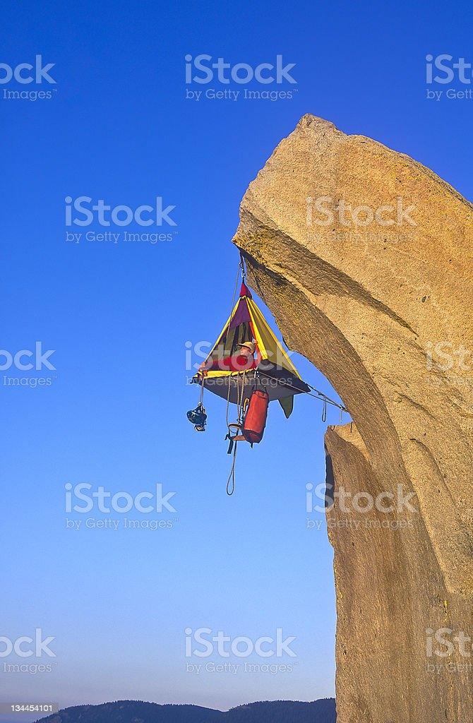Mountain climber and camp dangling from a cliff royalty-free stock photo