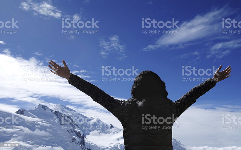 An excited mountain climber open arms when she climb the mountain peak