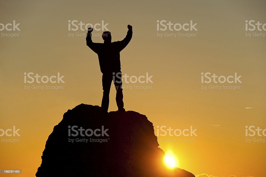 Mountain climber reaching the top at sunset royalty-free stock photo