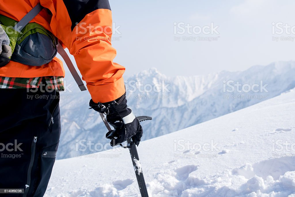 Mountain climber relaxes having reached the summit stock photo
