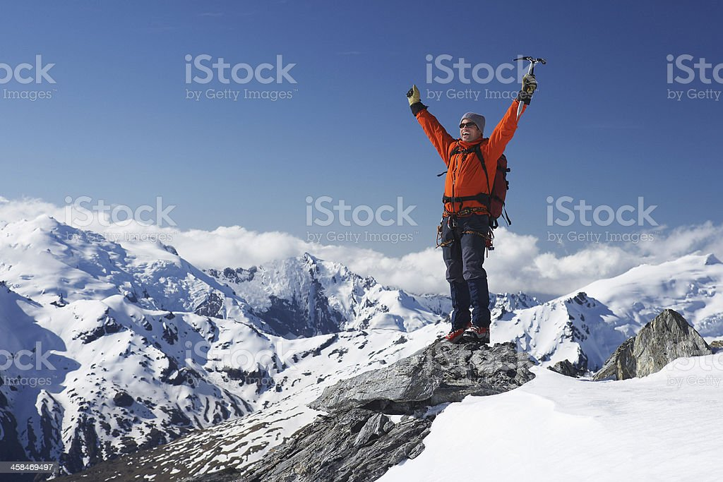 Mountain Climber With Arms Raised On Snowy Peak stock photo