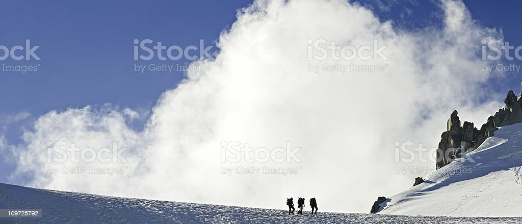 Mountain Climbers Walking Along Ridge Near Clouds royalty-free stock photo