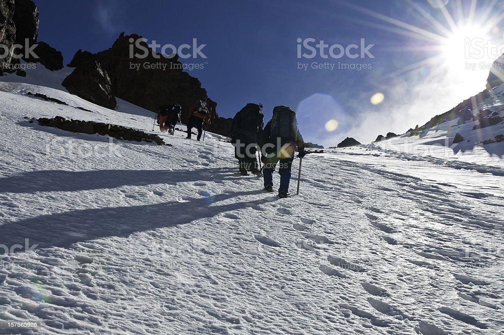 Mountain climbing snow summit sunburst high altitude mountaineering adventure stock photo