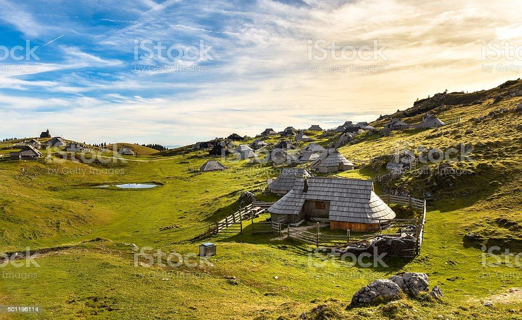 Mountain cottage on idyllic hill Velika Planina stock photo