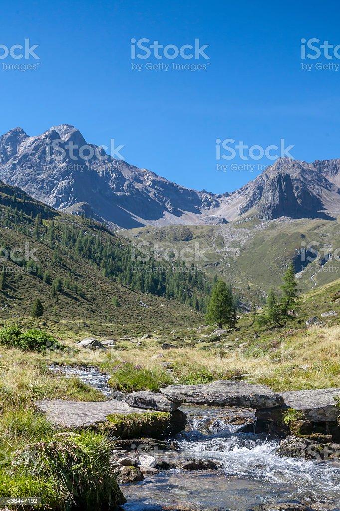 Mountain creek with stone bridge stock photo