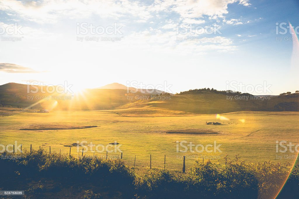 Mountain Hay Field at Sunset with lens flares. stock photo