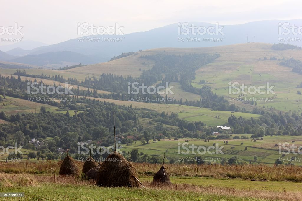 Mountain highland view with the haystacks in summer stock photo