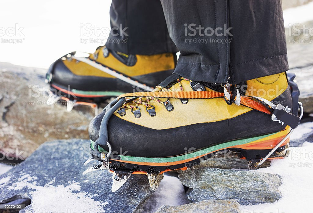 Mountain hiking boots with crampons stock photo