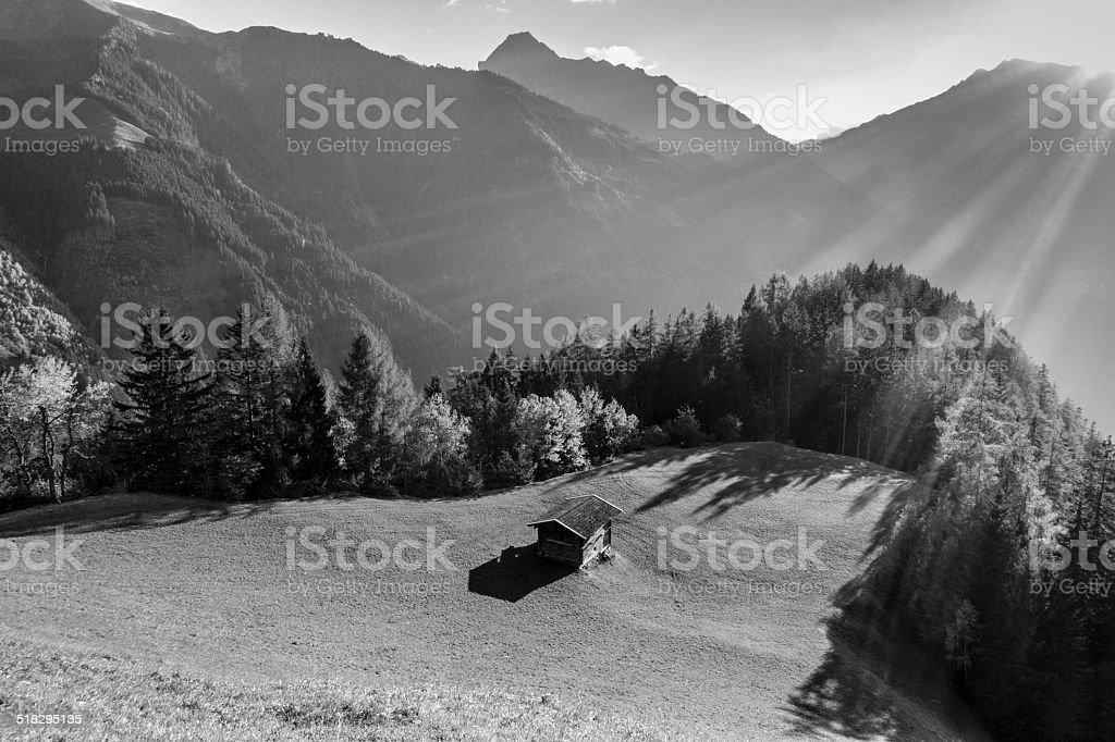 Mountain hut on autumn forest clearing in black and white stock photo