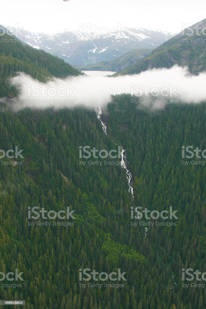 Mountain Lake Above the Clouds and Waterfalls Below stock photo
