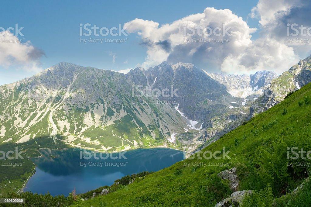 Mountain lake against the mountain slopes and sky stock photo