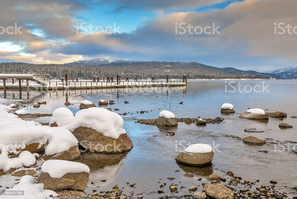 Mountain lake and boat doc winter with snow royalty-free stock photo