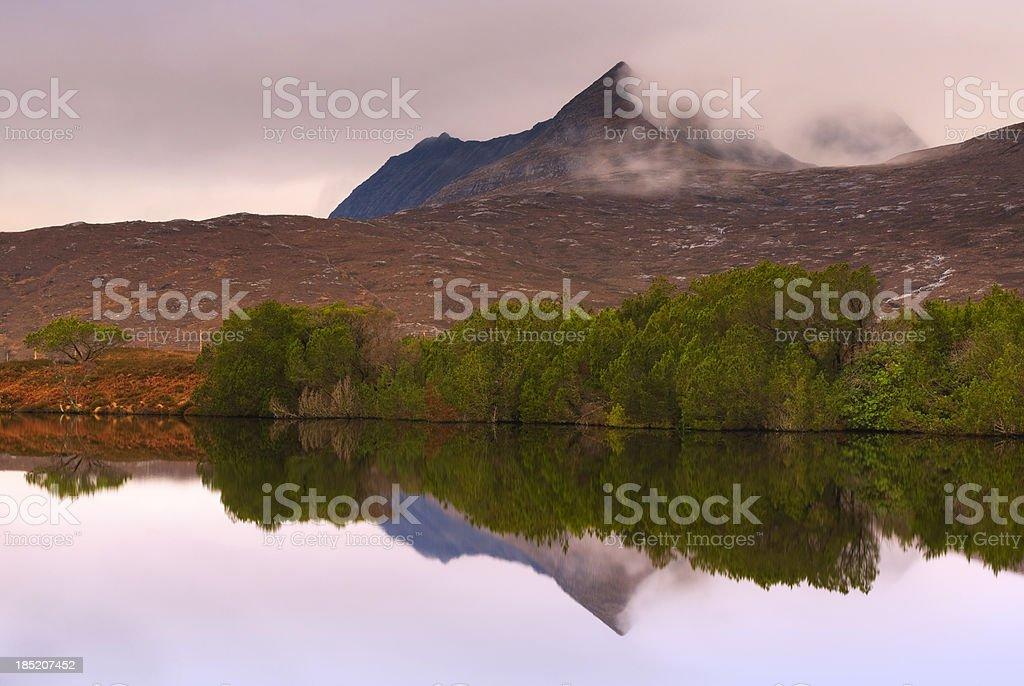 Mountain lake reflections at sunrise Scottish highlands stock photo