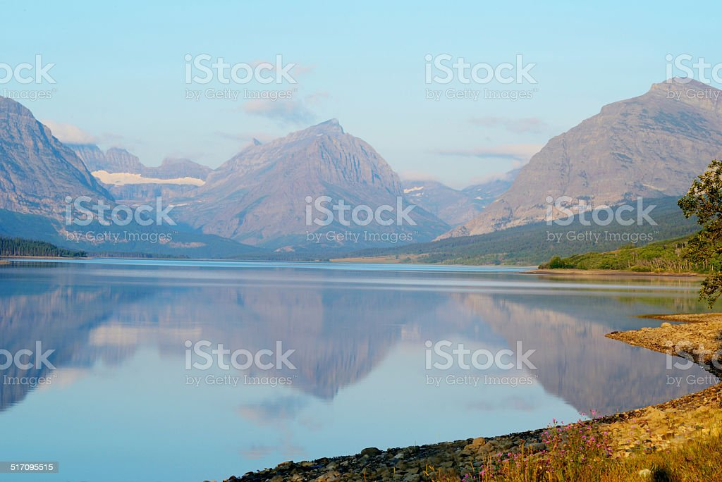 Mountain lake reflections in Glacier National Park. stock photo