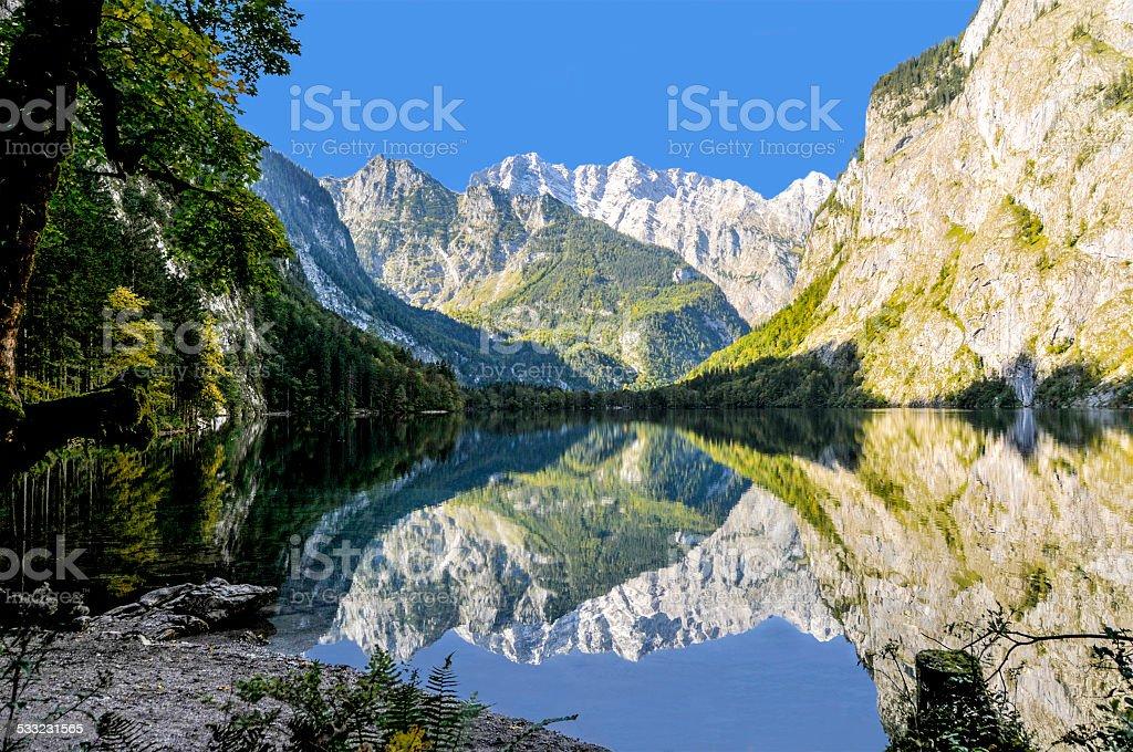Mountain lake surrounded mountain-range dramatic reflection stock photo