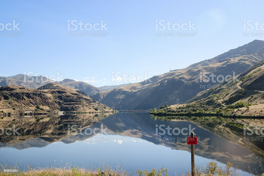 Mountain lake with reflections and danger sign stock photo
