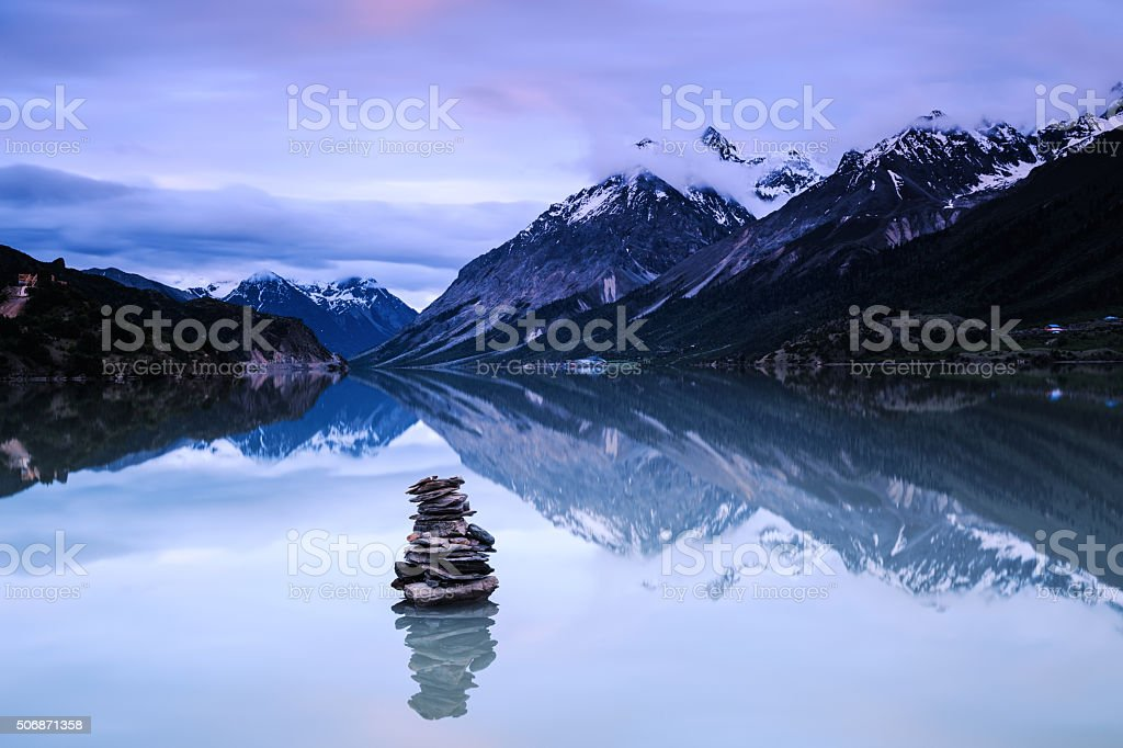 Mountain lake with stacked stones stock photo