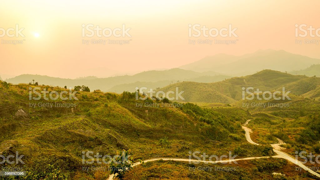 mountain landscape and valley road with orange sky at sunset stock photo