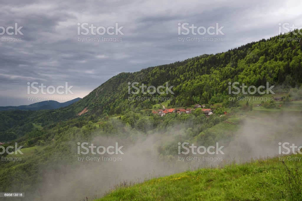 Mountain landscape shortly after spring rain. Slovenian Alps. Forest Road, venerable tree, fog, clouds and peaks. The village of Jamnik Slovenia. stock photo
