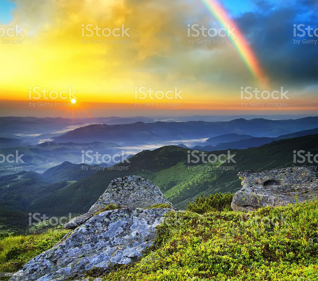 Mountain landscape with a rainbow in the sky during sunset stock photo