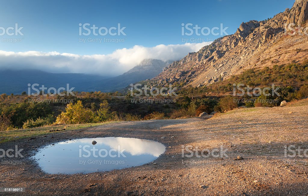 Mountain landscape with blue sky reflection in puddle at sunset stock photo