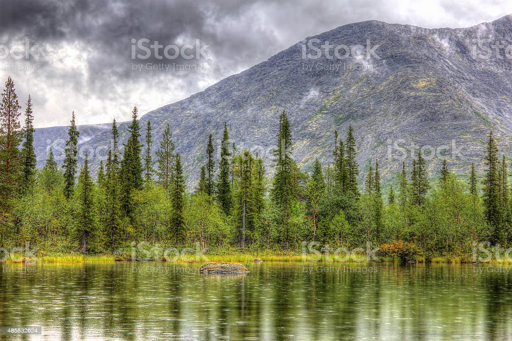 mountain landscape with lake, forest and clouds, rainy weather, HDR stock photo