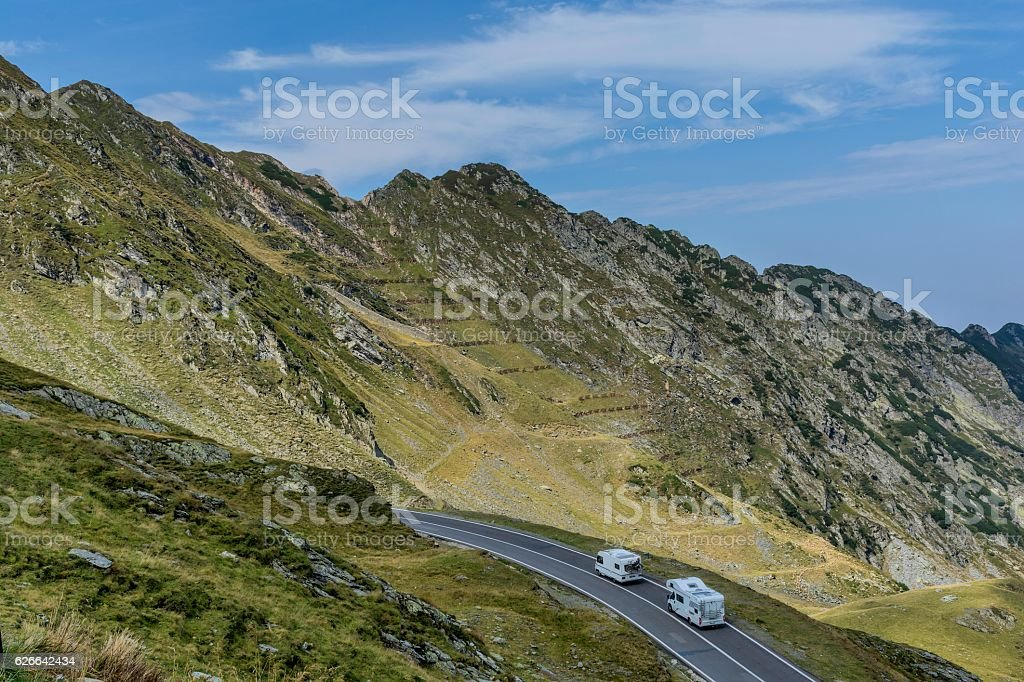 Mountain landscape with road and moving caravan travel trailers. stock photo