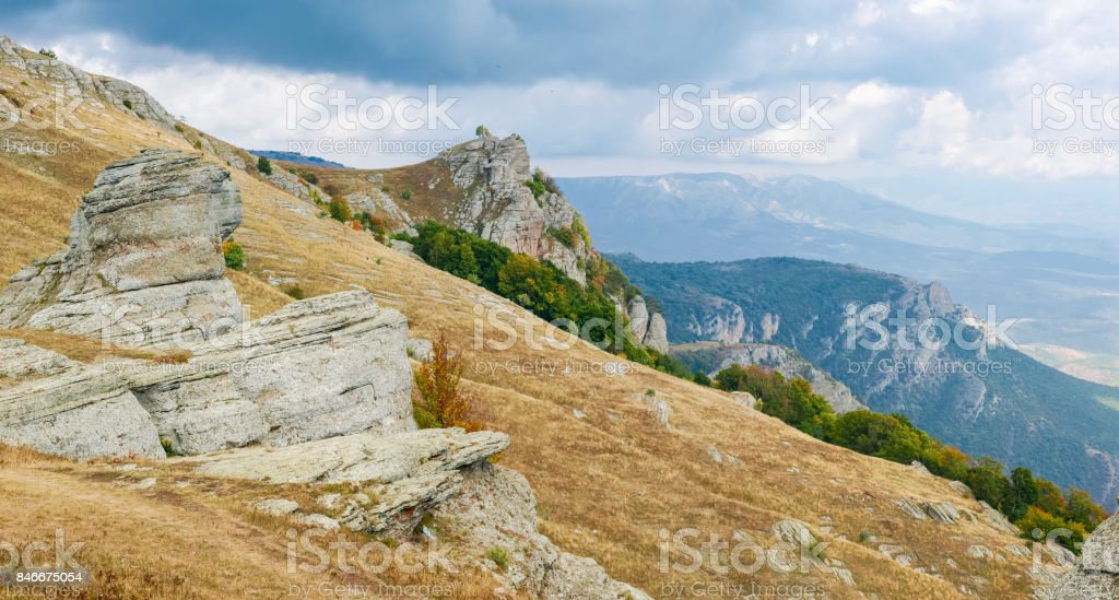 Mountain landscape with weathered rocks on a grassy slope on a...