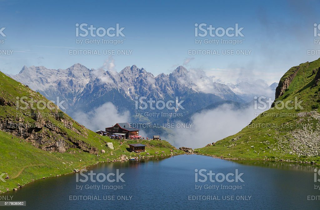 Mountain lodge at edge of lake stock photo