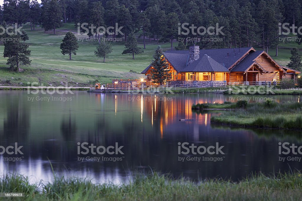Mountain Lodge Reflecting in Lake at Dusk stock photo