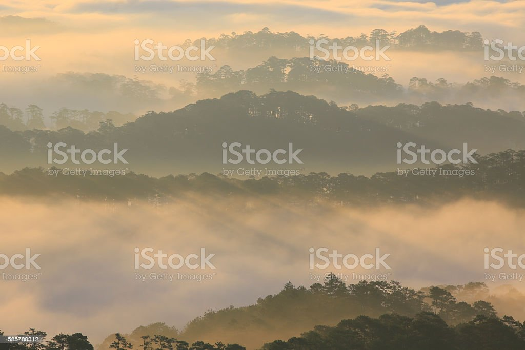 Mountain, mist and sunlight at dawn stock photo
