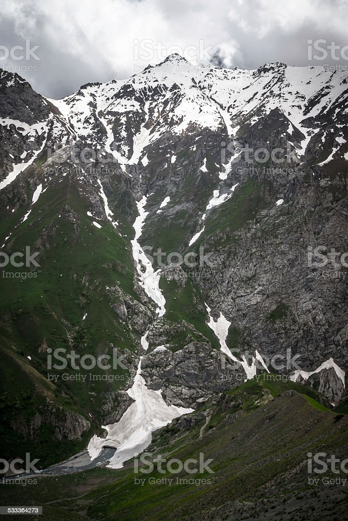 Mountain pass with the glacier and green grass. Fann Mountains. stock photo